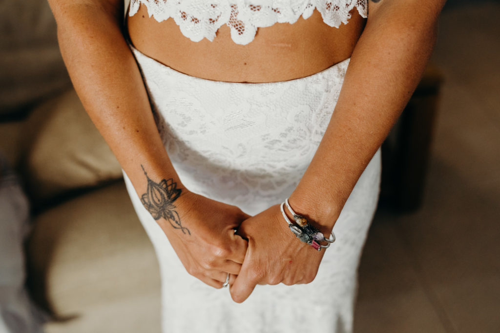 bride in two piece wedding dress holding her hands just before her Riddell Beach wedding in Broome