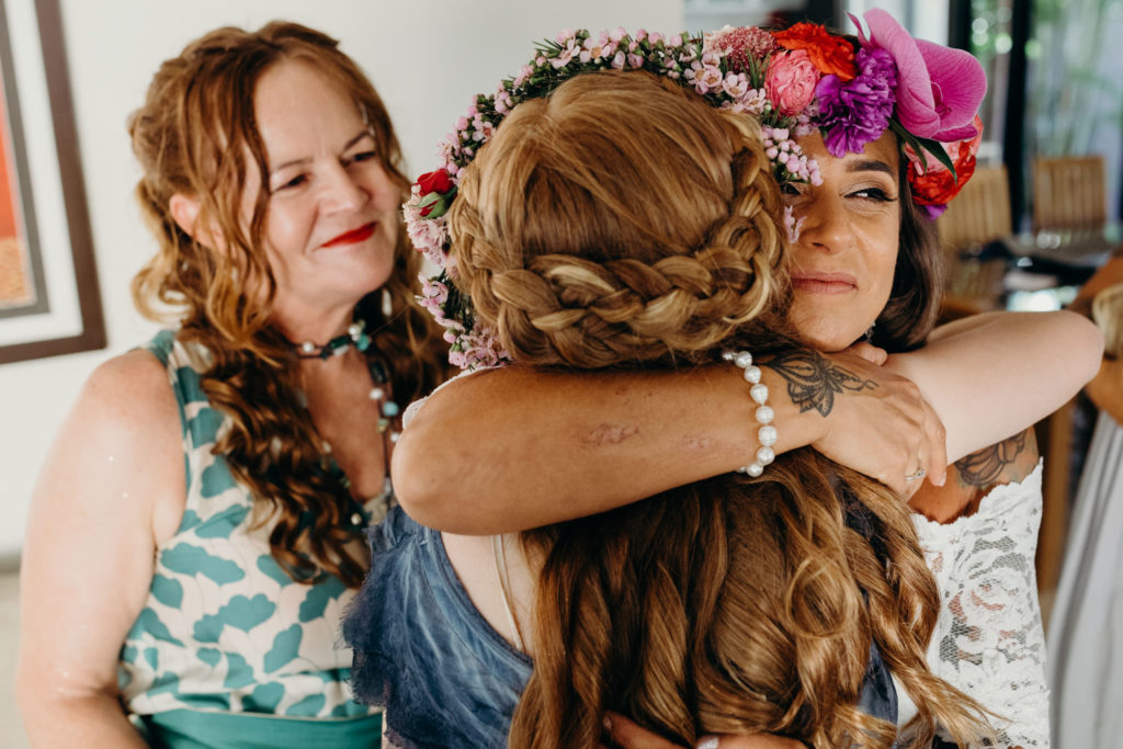 bride hugging her girlfriends on her wedding day