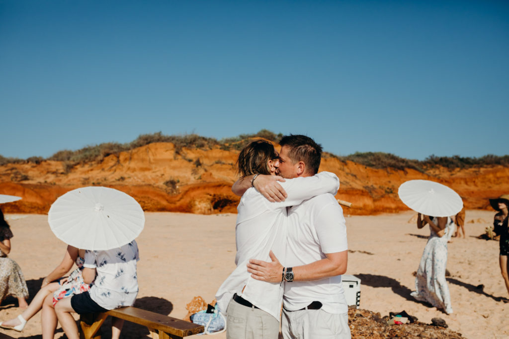 two men in white short hugging at beach wedding