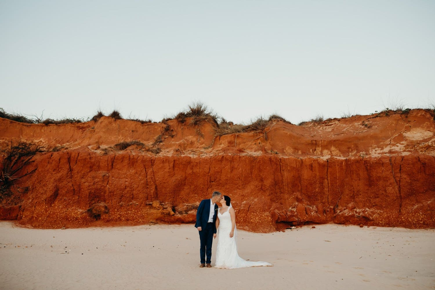 Broome wedding couple portrait in front of a red pindan cliff in Broome Western Australia