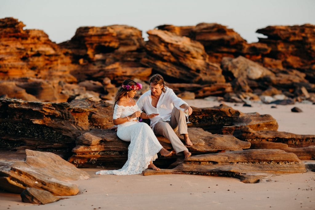 a young wedding couple sits on rocks on the beach in Broome looking at her new wedding ring