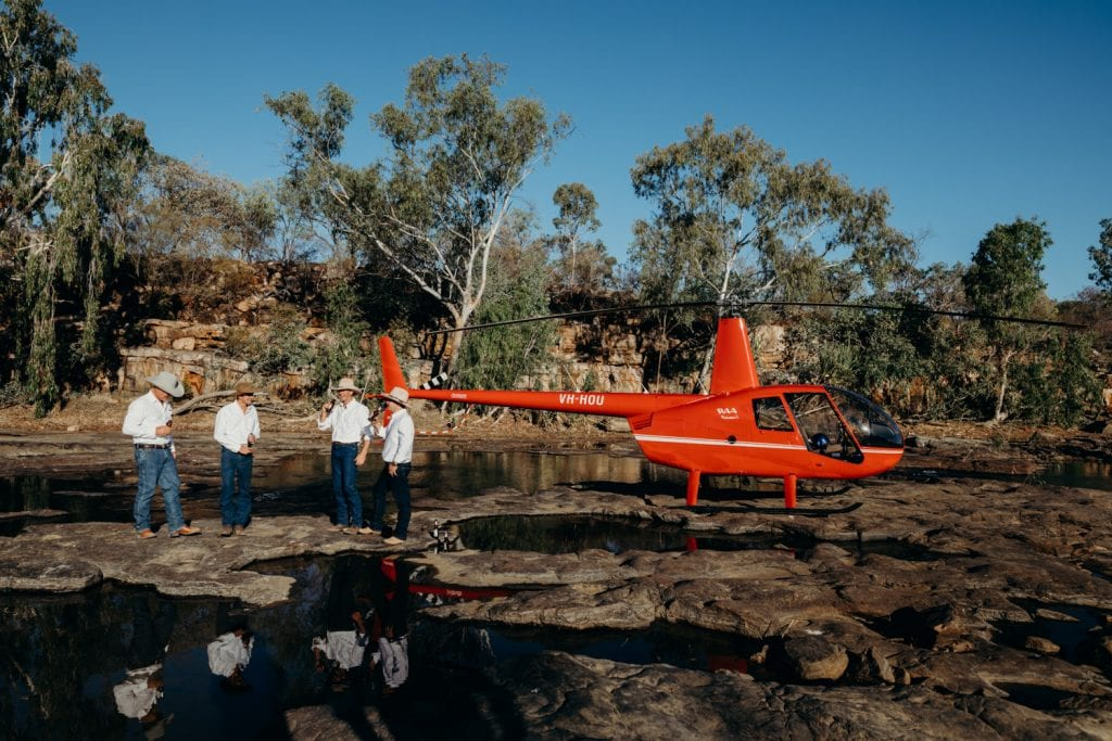 groom and his groomsmen standing next to a red helicopter at a Kimberley wedding in Western Australia