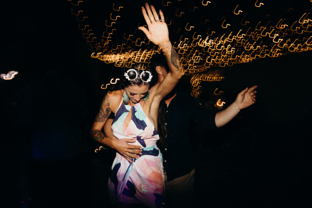 woman wearing white sunglasses and summer dress dances under the night sky at Viv and Matt's Broome wedding