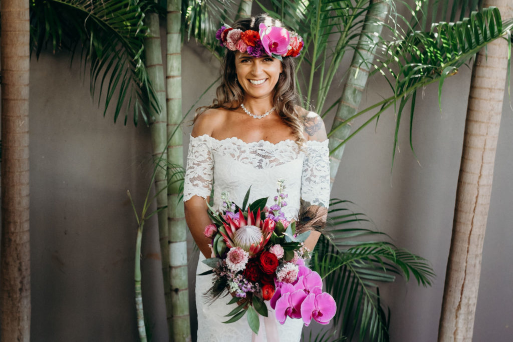 bride in two piece wedding dress by Grace Loves Lace stands in front of palm wearing a beautiful flower crown with orchids and holding a large flower bouquet by Broome Florist