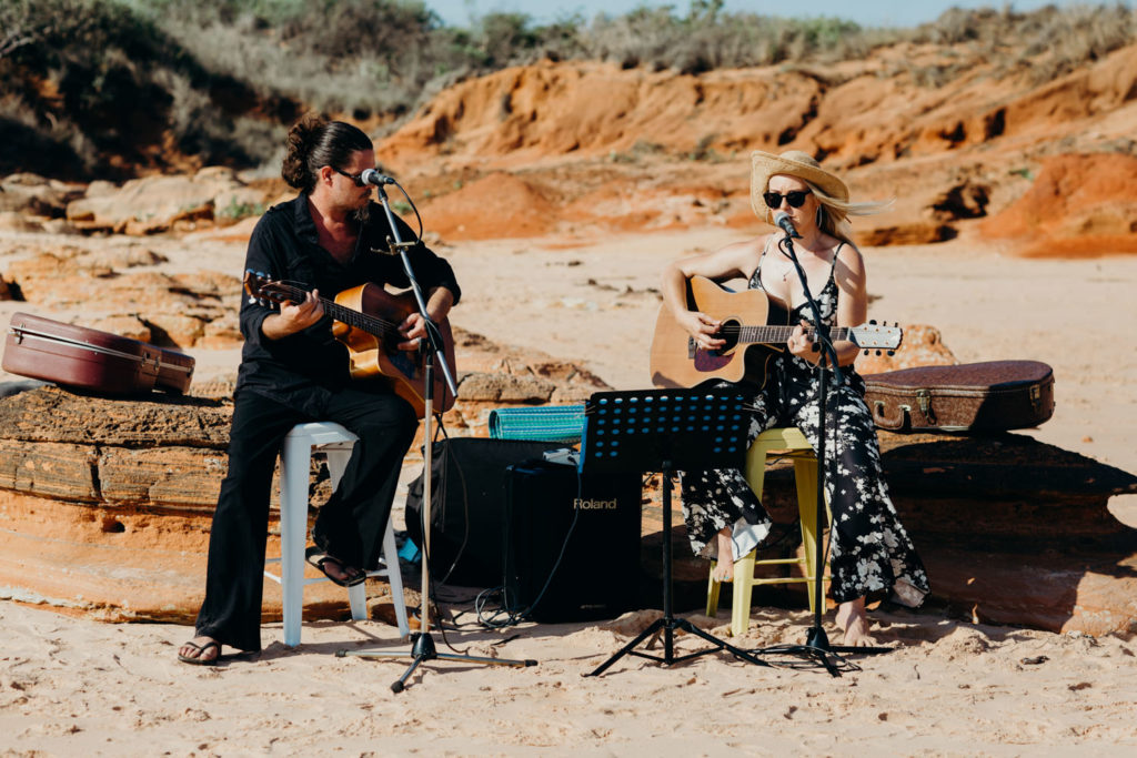 Two musicians set up on Riddell Beach playing music for wedding