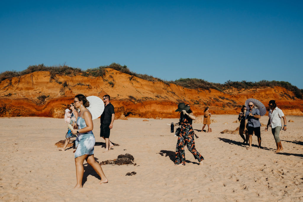 Wedding guests walking along the beach to make their way to the Riddell Beach wedding ceremony in Broome