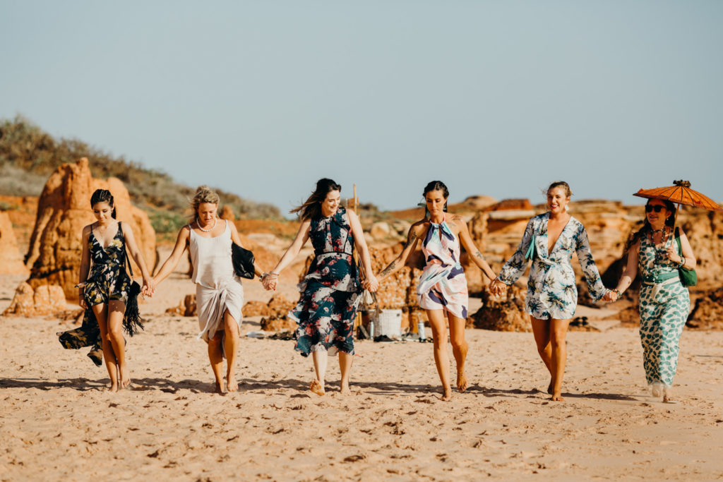 group of young women in summer dresses walking hand in hand along Riddell Beach to wedding ceremony