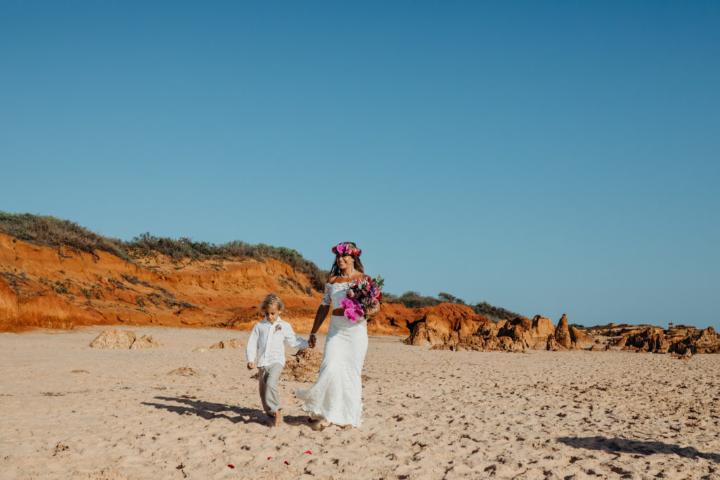 young boy walks his mum down the aisle at Riddell Beach wedding in Broome