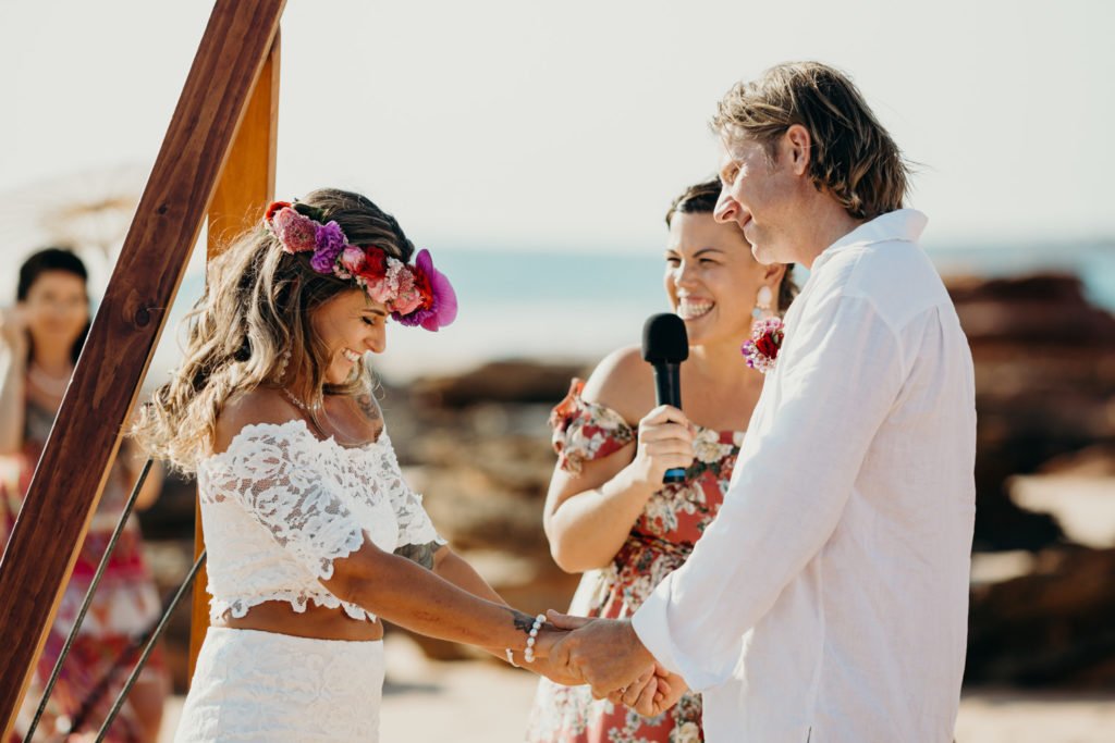 couple standing under a wooden arbour with Broome wedding celebrant Elle Saunders