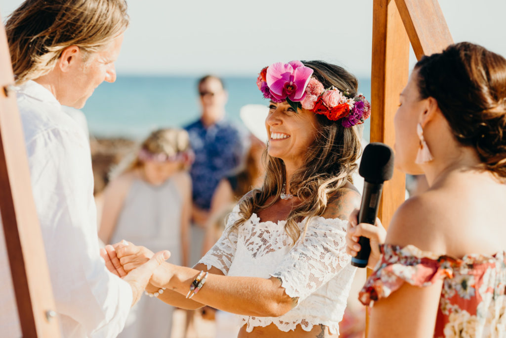 smiling bride holding hands of her groom during their Riddell Beach wedding ceremony in Broome in Western Australia