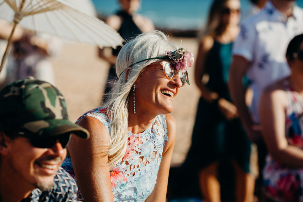 woman with flower crown and orange sunglasses watches ceremony at Riddell Beach ceremony in Broome