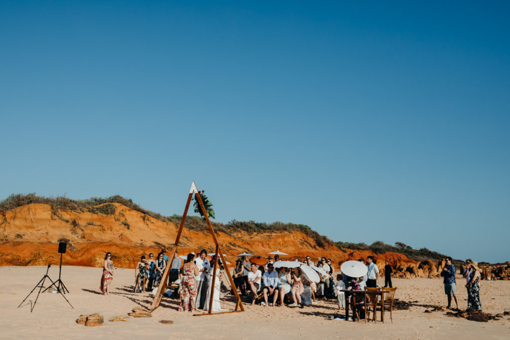 beach wedding ceremony with guests seated on benches and wedding couple standing under a wooden arbour with Elle Saunders wedding Broome celebrant