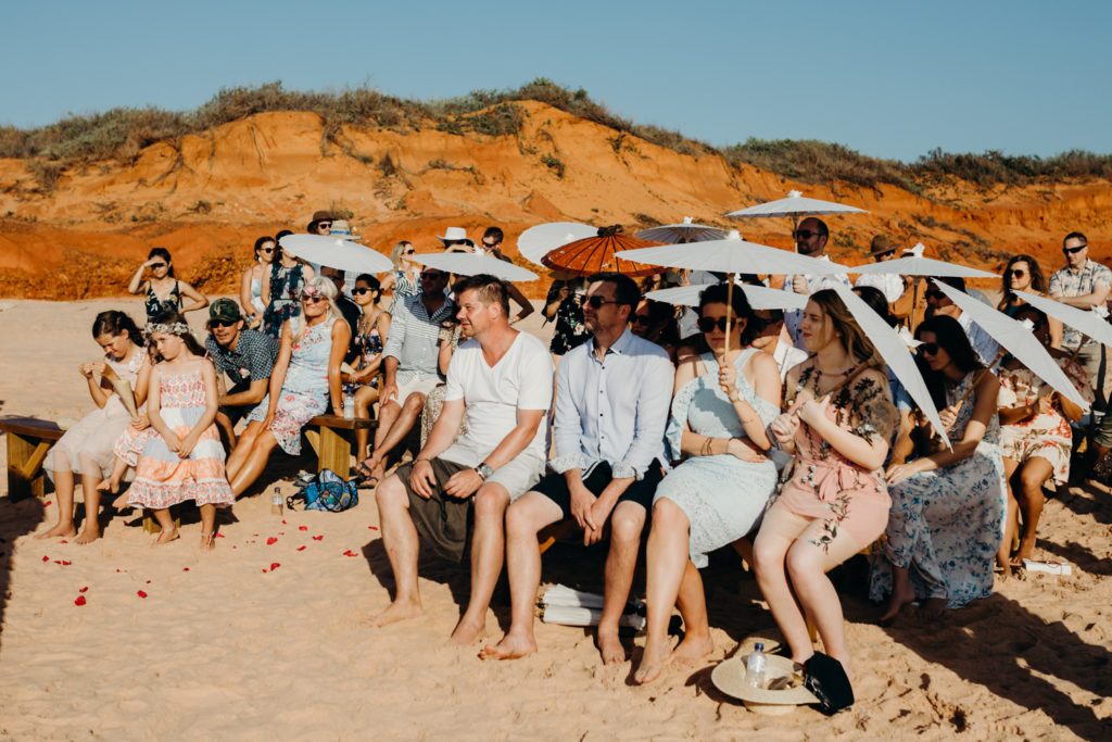 group of people seating on wooden benches on the beach watching a ceremony and holding white parasols on Riddell Beach wedding