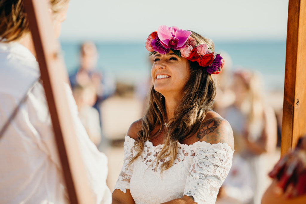 portrait of bride wearing a large flower crown looking at her groom and smiling
