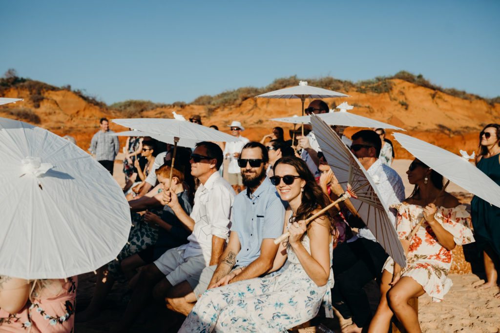 wedding guests seating on wooden benches in full sun on the beach with white parasols and wearing sunglasses