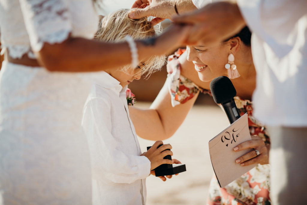 Broome wedding celebrant Elle Saunders bends down to talk to little boy who has wedding rings in box