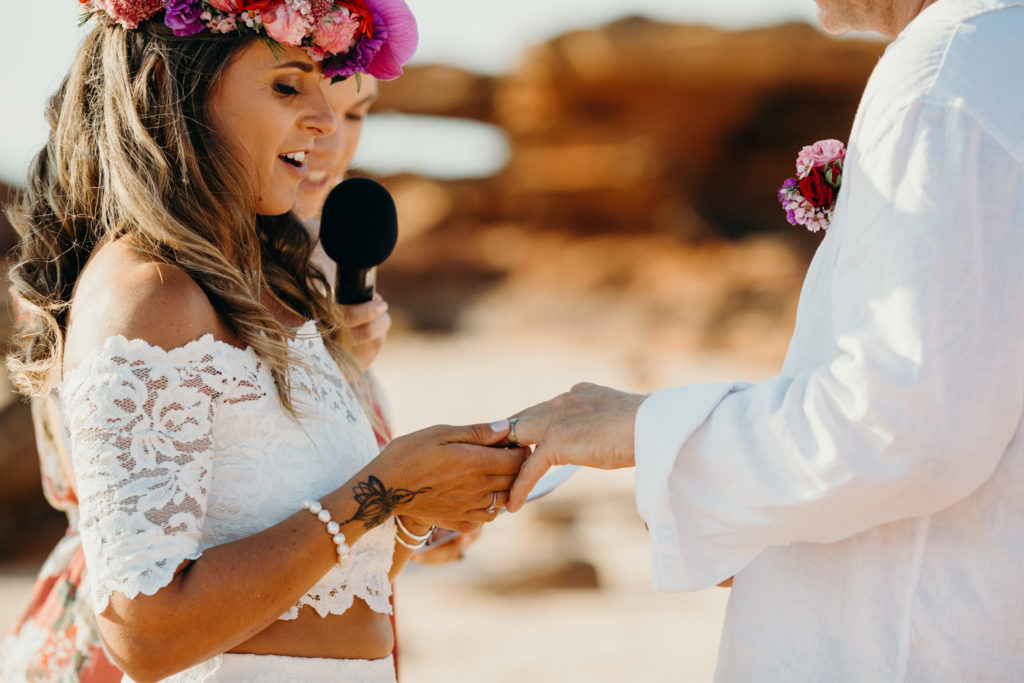 bride places wedding ring on her groom's finger at Riddell Beach wedding in Broome Western Australia