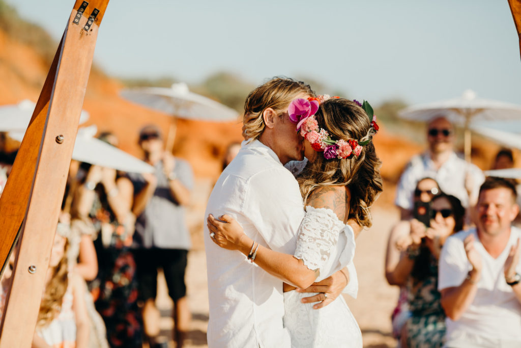 wedding couple kisses under a wooden arbour at the Riddell Beach wedding with their guests in the background cheering and clapping