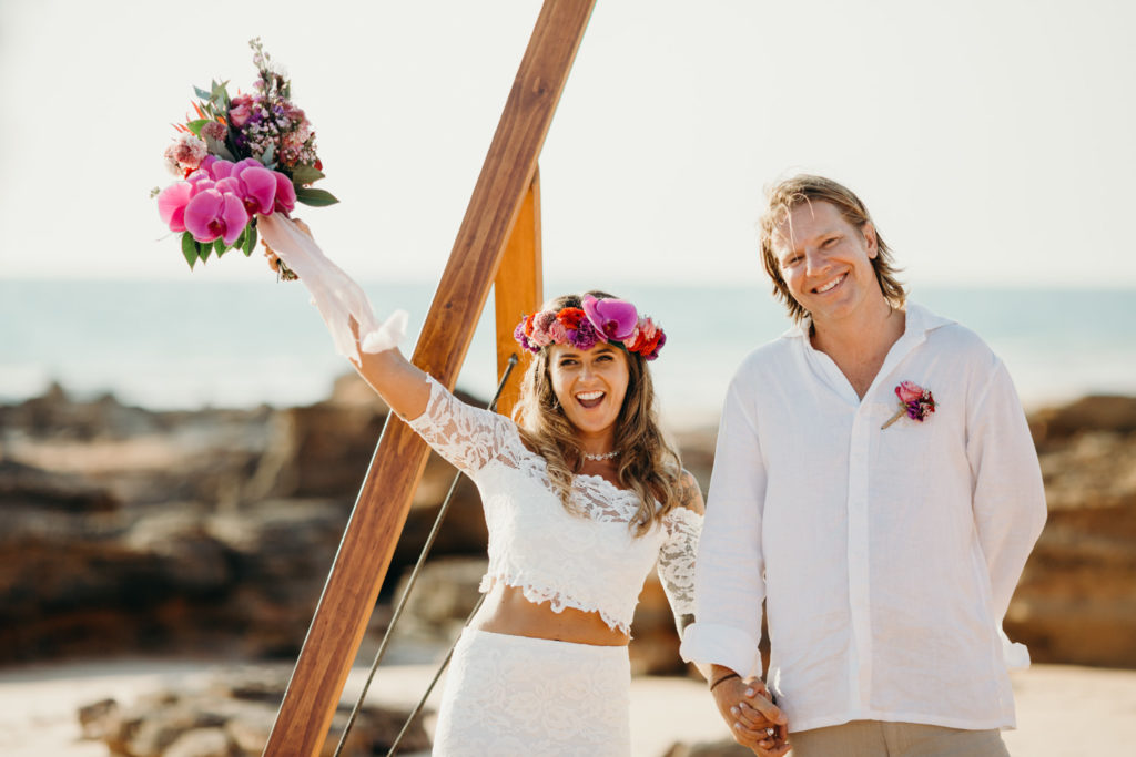 young wedding couple standing under wooden arbour with ocean as backdrop and bride throwing arm in the air while holding her flower bouquet