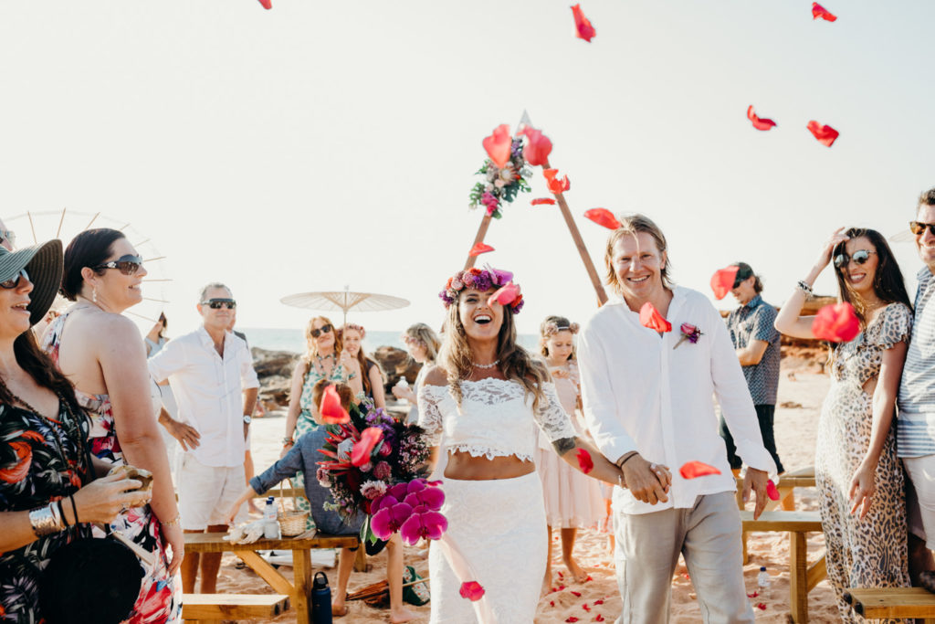 wedding couple walks back down the aisle with wedding guests throwing flower petals at them on Riddell Beach