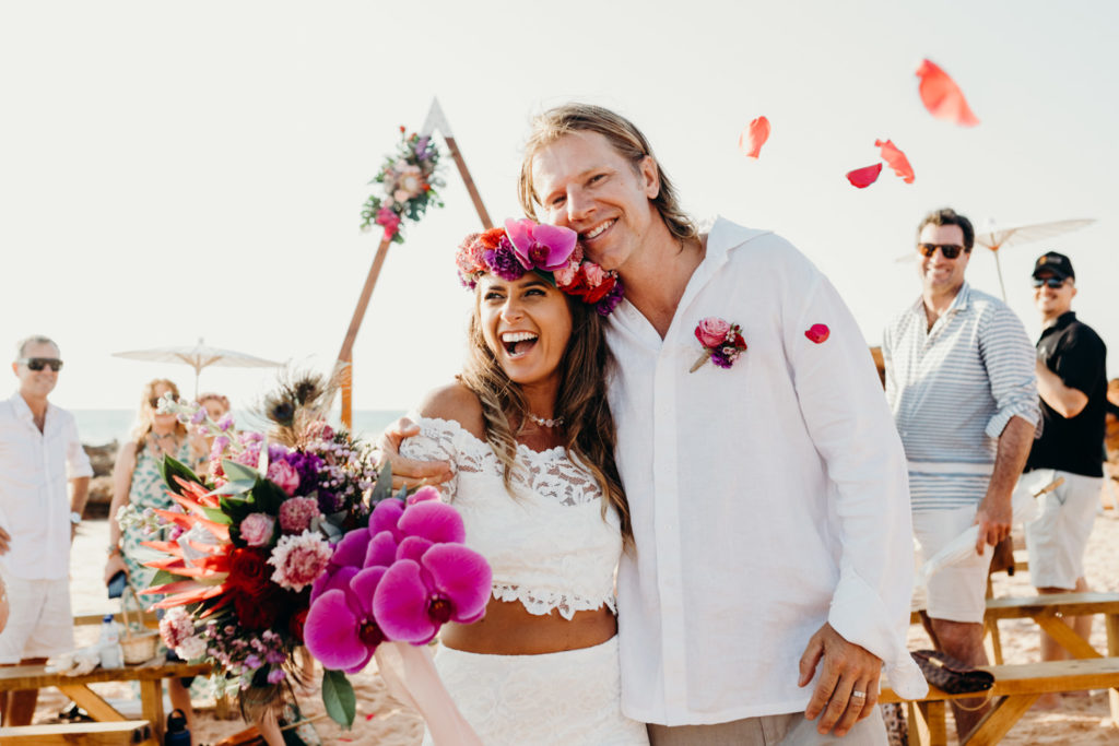 young wedding couple stand on the beach, both smiling and very happy
