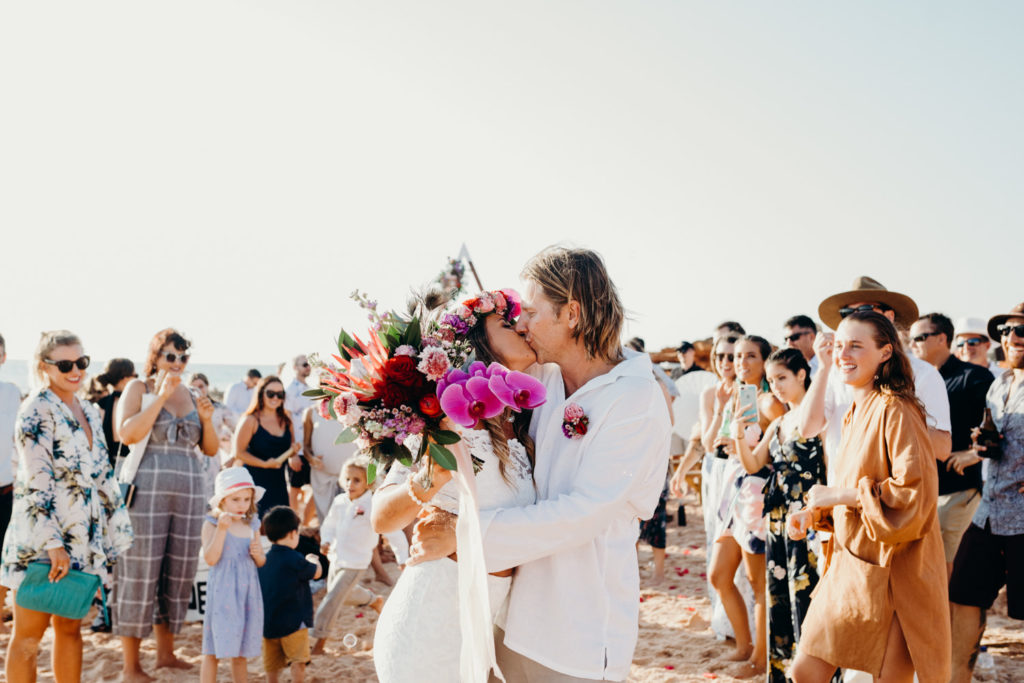 couple kisses in front of their wedding guests at their beach wedding in Broome