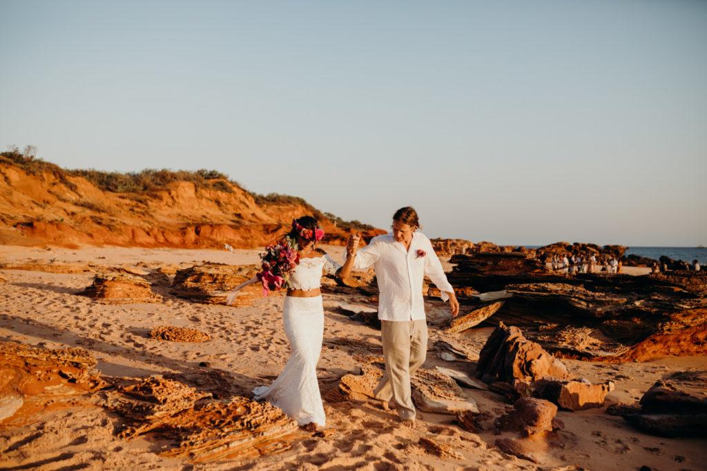 groom in white linen shirt leads his bride across Riddell Beach