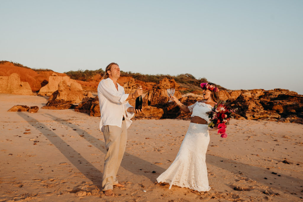 bride and groom pop open a bottle of champagne on the beach with the cork flying high