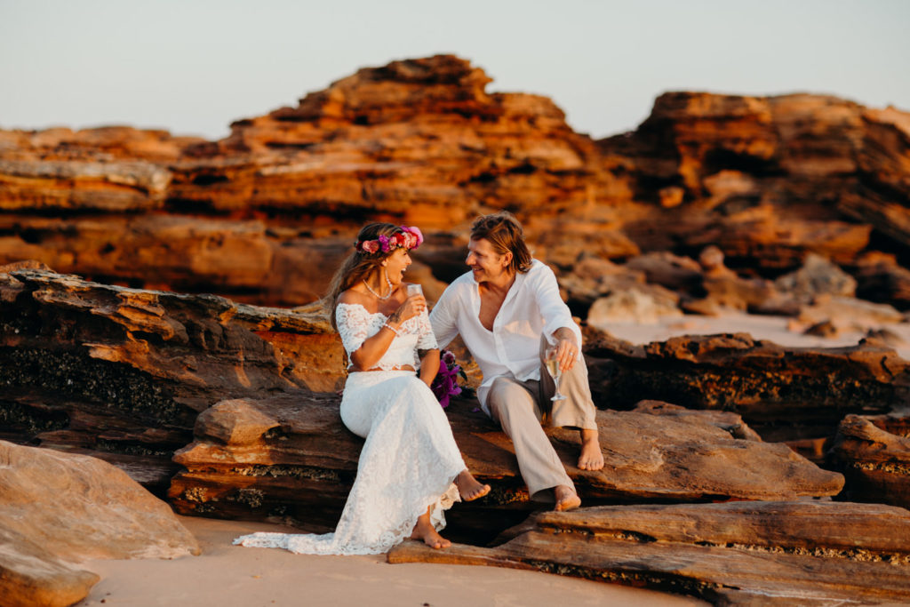 young couple sits on rocks at their Riddell Beach wedding and enjoy a glass of champagne