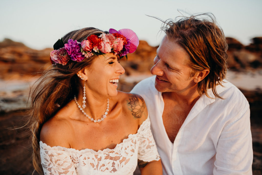 freshly hitched wedding couple sits close to each other with bride wearing a colourful flower crown and groom a white shirt