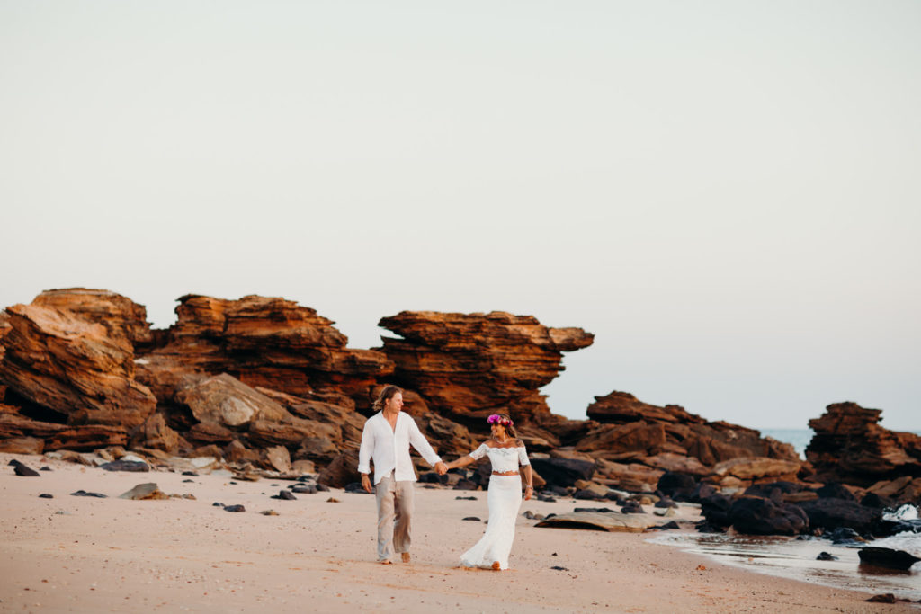couple walk hand in hand along Riddell Beach in Broome on their wedding day