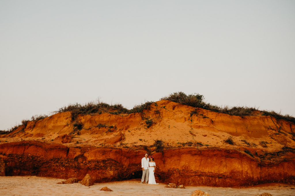 wedding couple stands in front of a large, red pindan cliff at Riddell Beach wedding