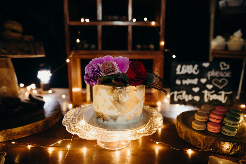 wedding cake decorated with purple orchids and fairy lights