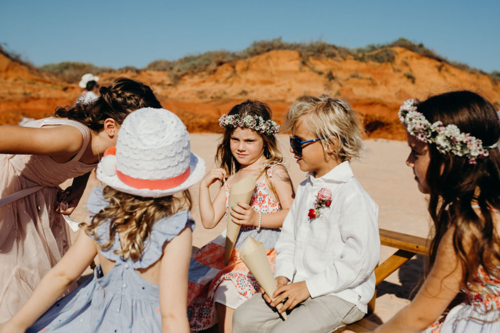 group of children at beach wedding at Riddell Beach in Broome with young boy in the centre holding a cone full of flower petals