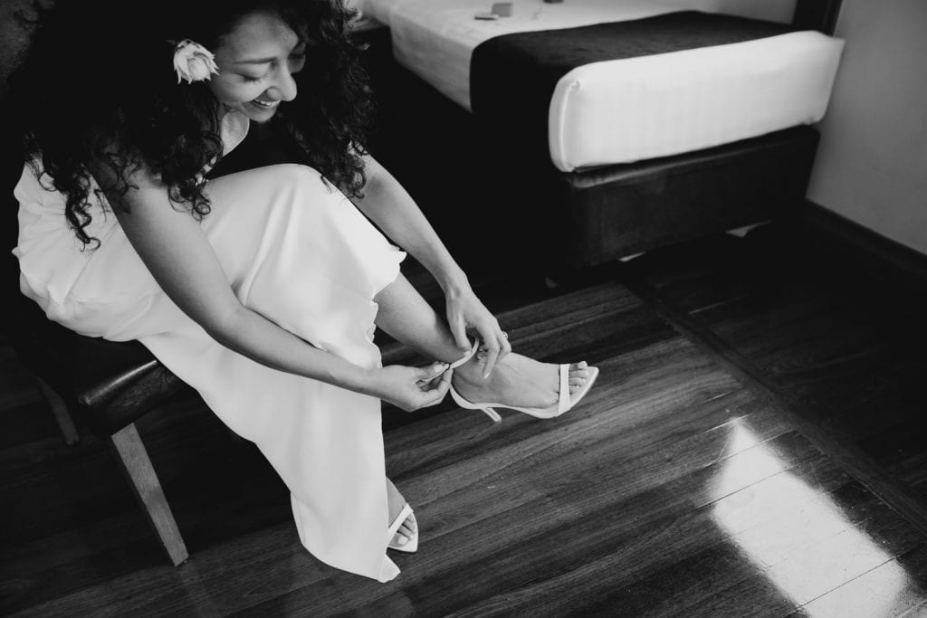bride is sitting down and putting on shoes to go to her broome church wedding