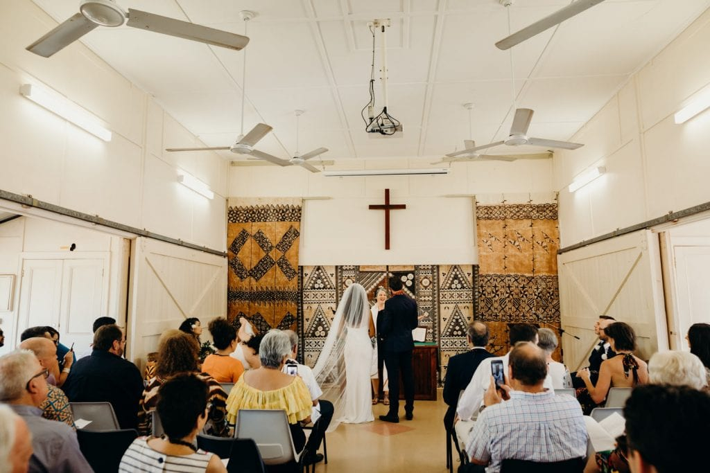 bride and groom stand in Broome church wedding with wedding guests seated