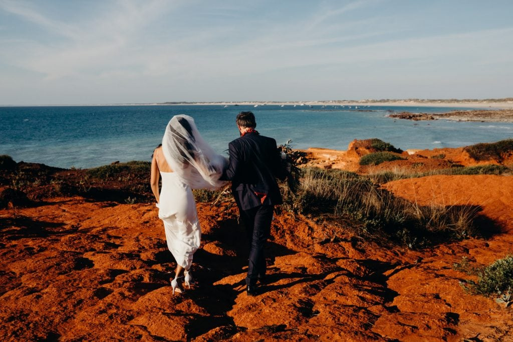 bride and groom in wedding attire walking on red rocks at Gantheaume Point in Broome after their Broome church wedding