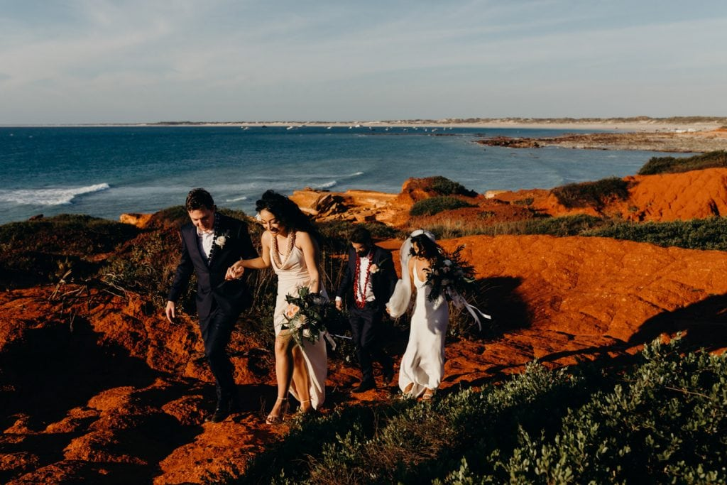 bridal party walks along rocky path in Broome with ocean views
