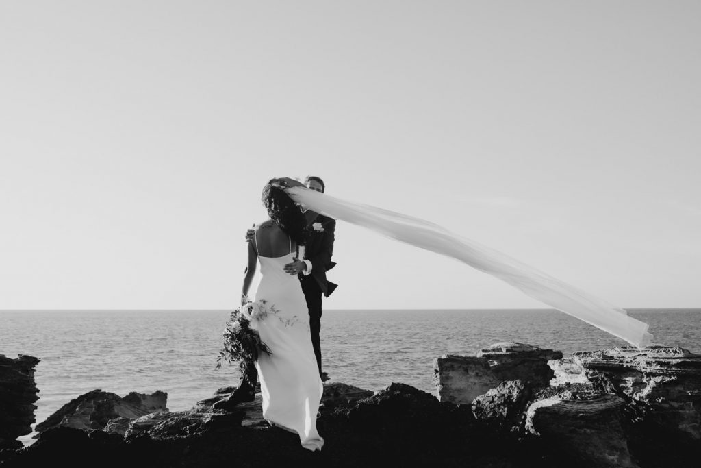 black and white photo of bride and groom standing on the cliff edge with veil flying to the side