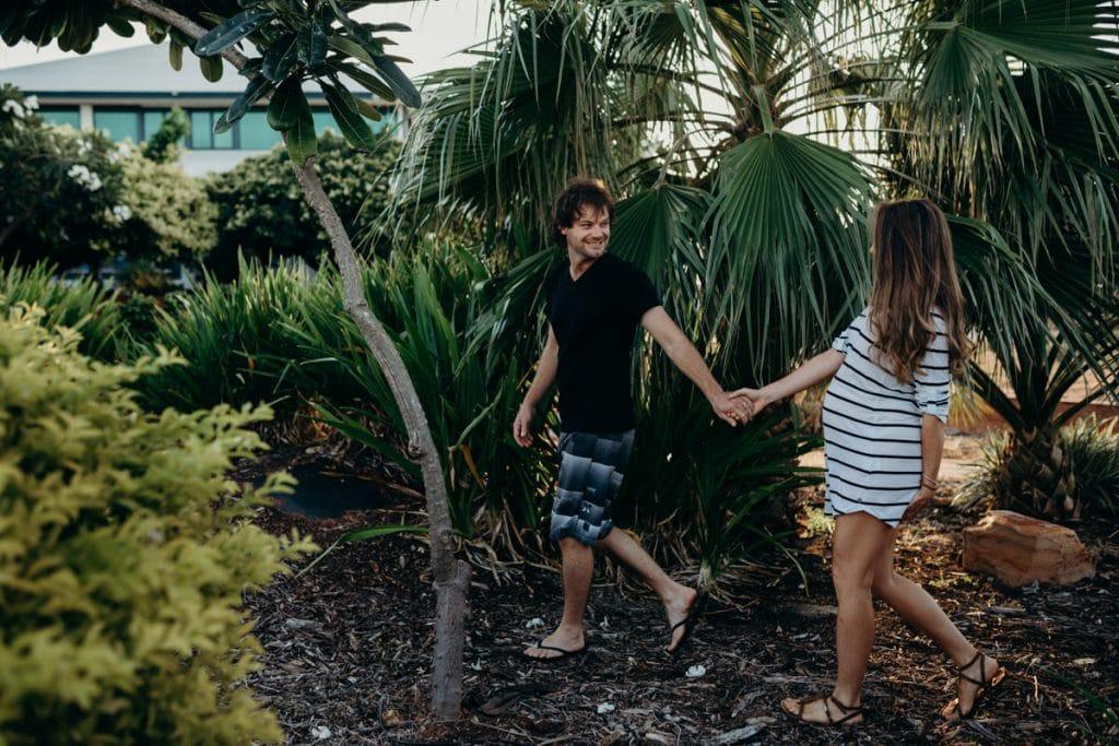 young couple walks among palm trees at Broome Port