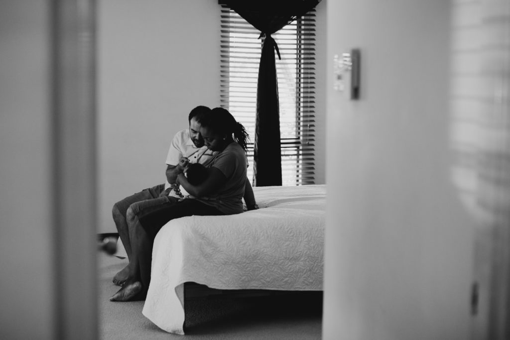 young couple sits on the edge of the bed, holding their newborn baby