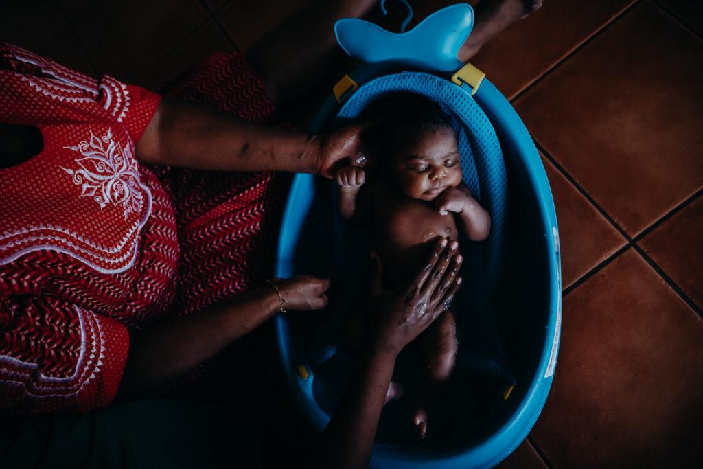 newborn baby being bathed