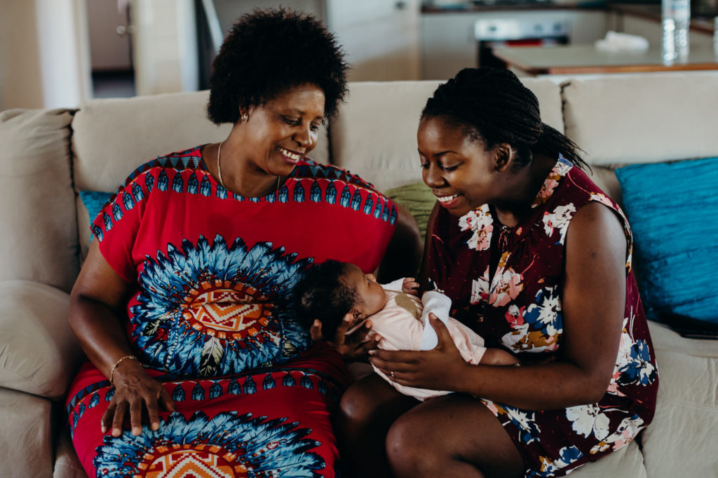 mother and daughter sitting on couch with newborn baby