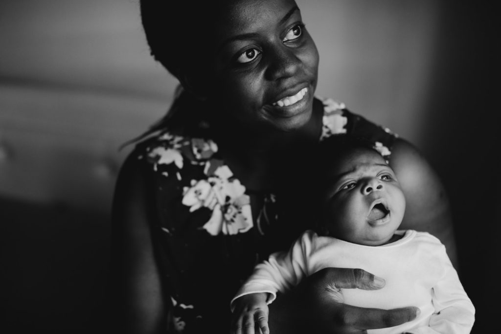 photo of woman with her newborn baby by the window