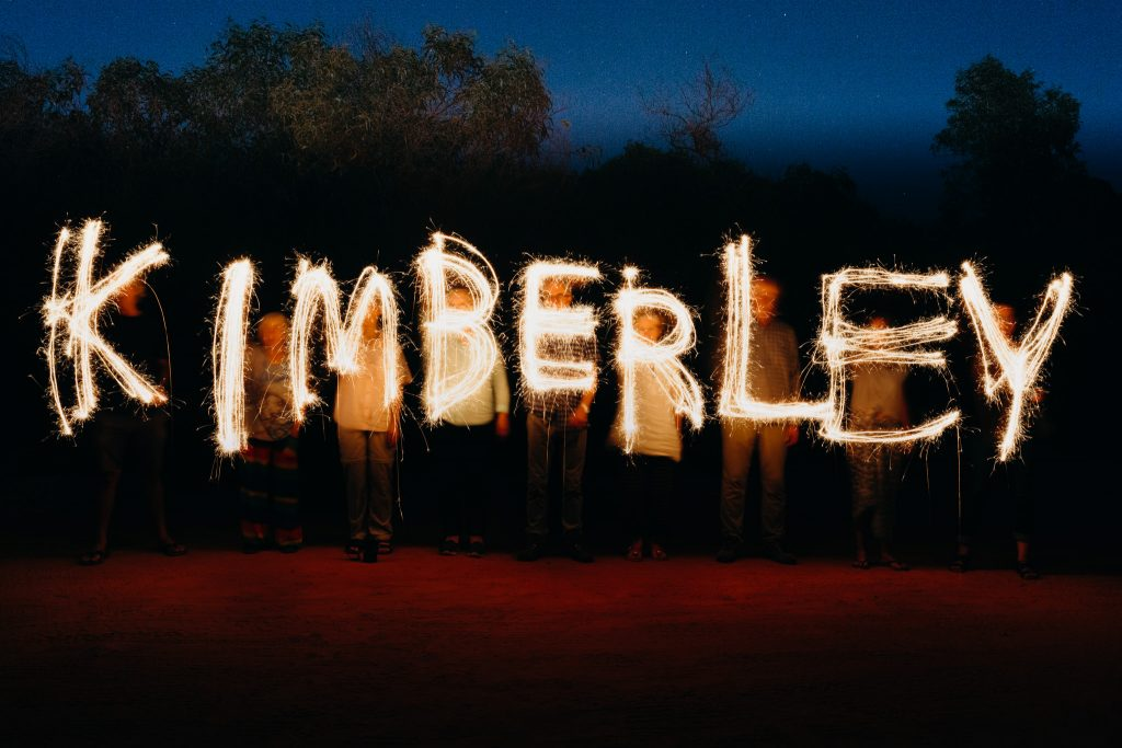 group of people with sparklers at night writing the word Kimberley as a light painting