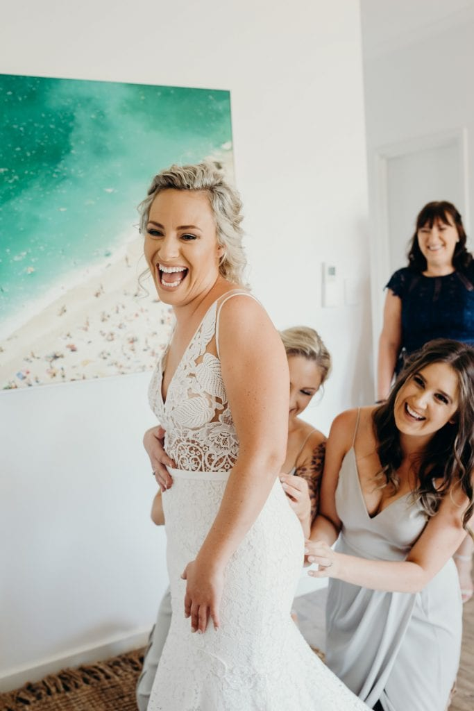 laughing bride is getting into her dress