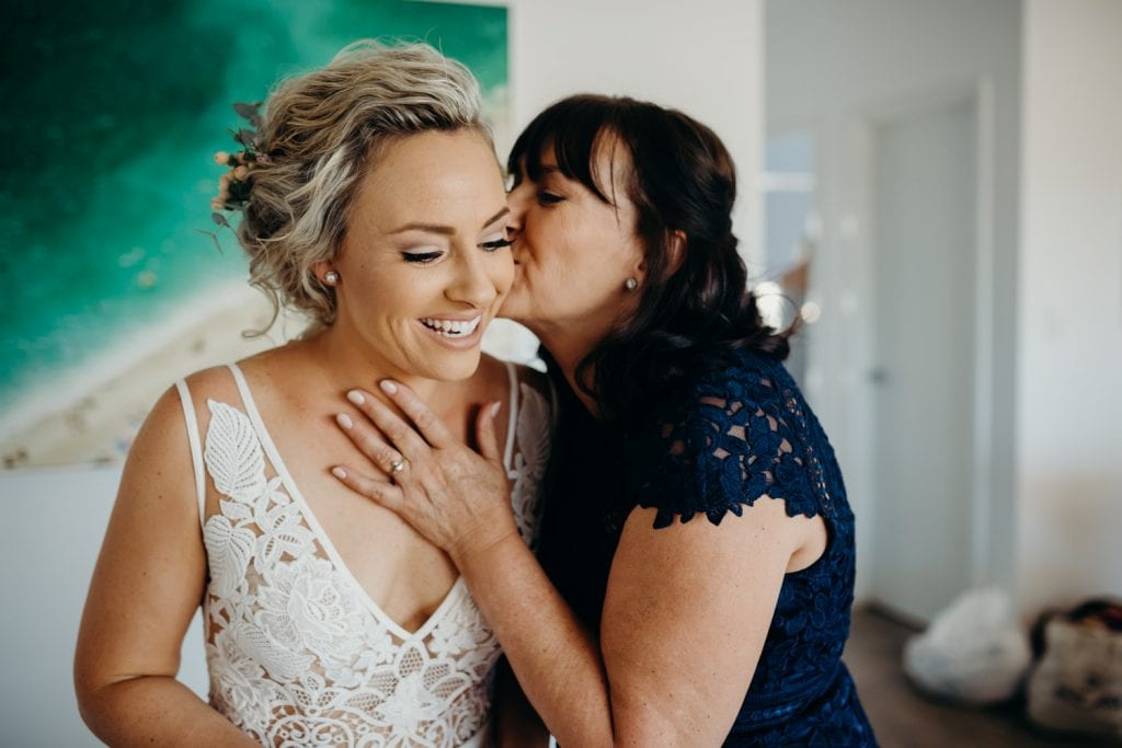 mother kisses her daughter on the cheek at the getting ready on wedding day