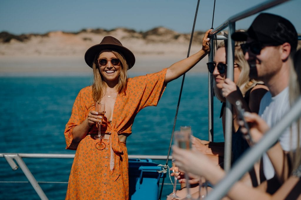 smiling young woman on Broome whale watching boat in orange dress and brown broad-brimmed hat