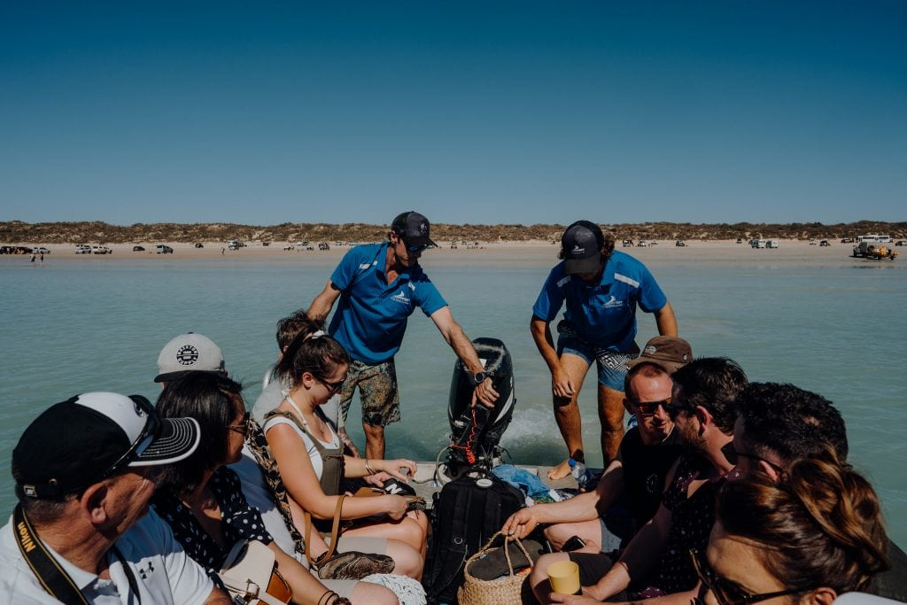 group of people travels in small boat to head out to main Broome whale watching vessel of Cable Beach