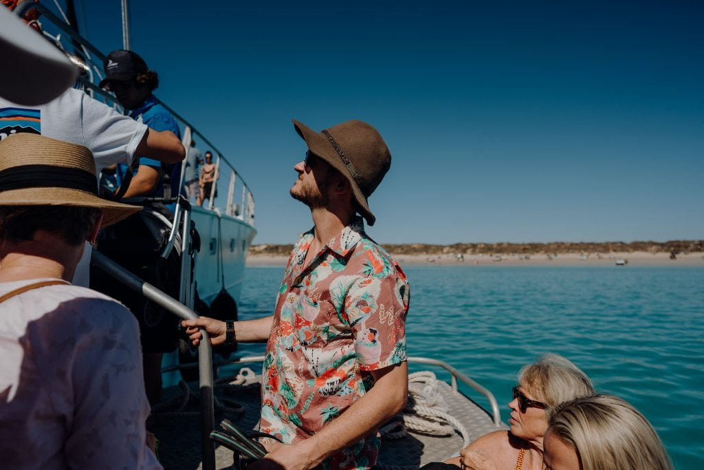 young man in brown hat and colourful shirt looks up to Broome Whale Watching boat
